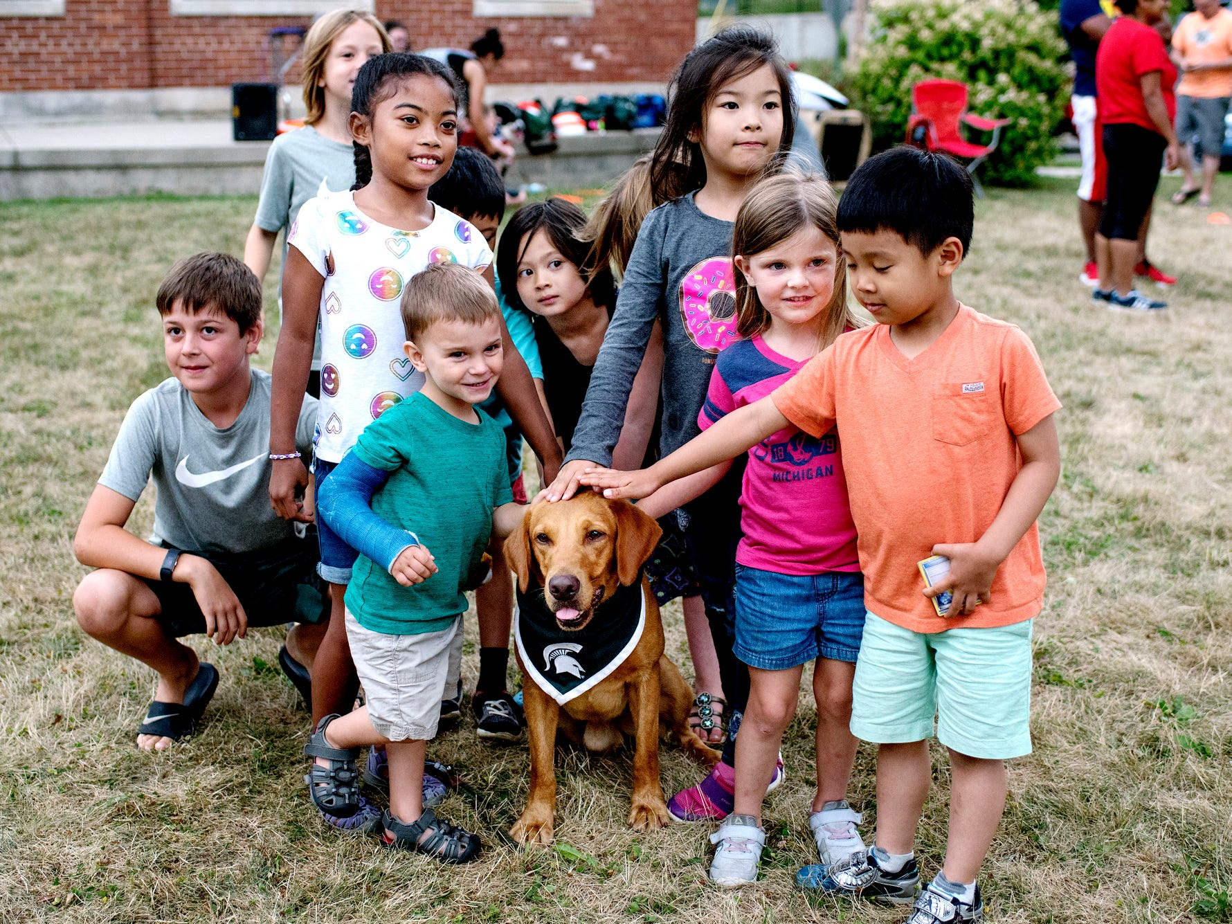 Children gather around Zeke the Wonderdog IV for photos after a performance at Play in the Park on Tuesday, July 31, 2018, at Valley Court Park in East Lansing.