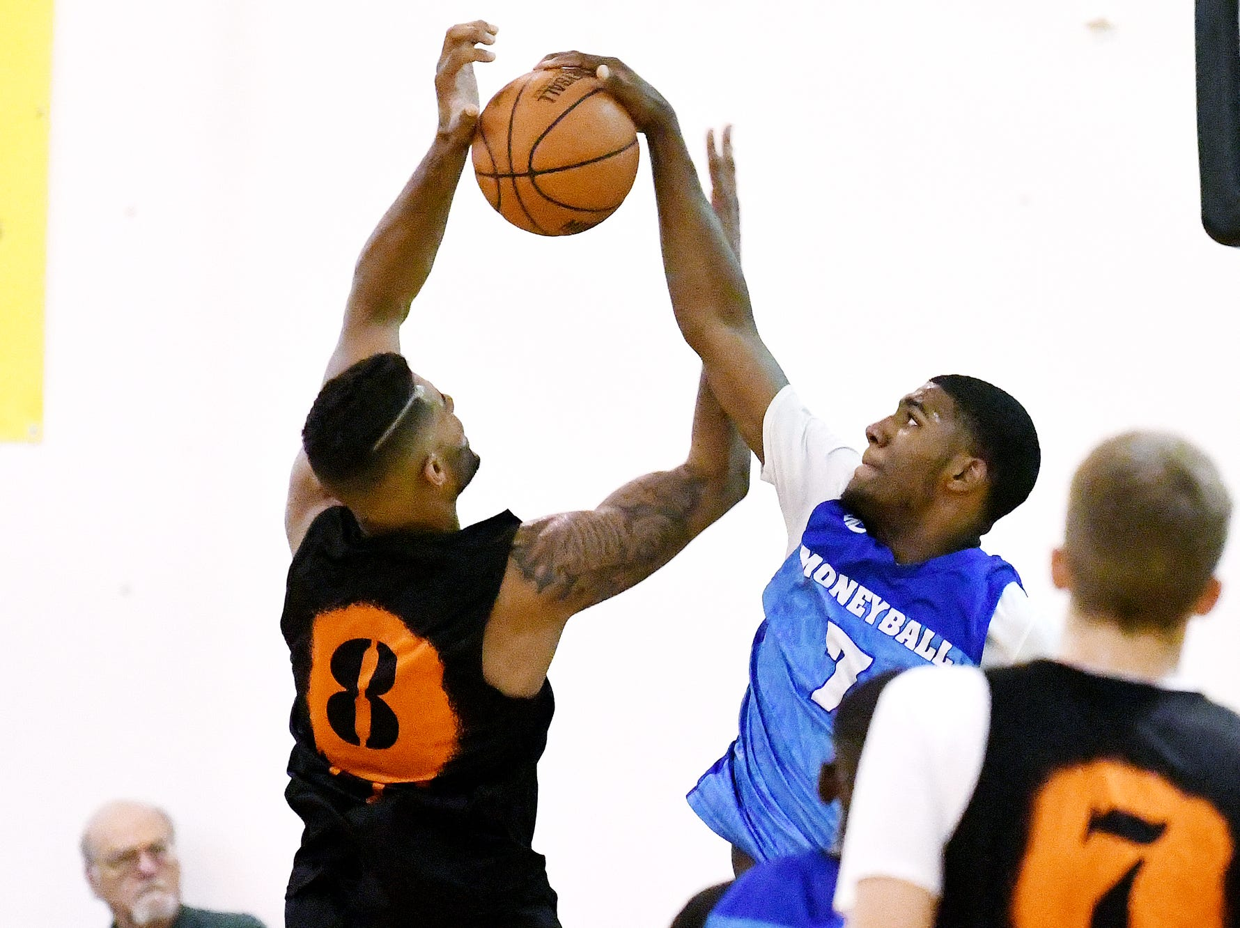 Team Definition's Aaron Henry, right, blocks a shot by Team Splatter's Devin Oliver on Thursday, Aug. 2, 2018, during the Moneyball Pro-Am summer basketball league championship game at Aim High in Dimondale. Team Definition won the game 99-83.