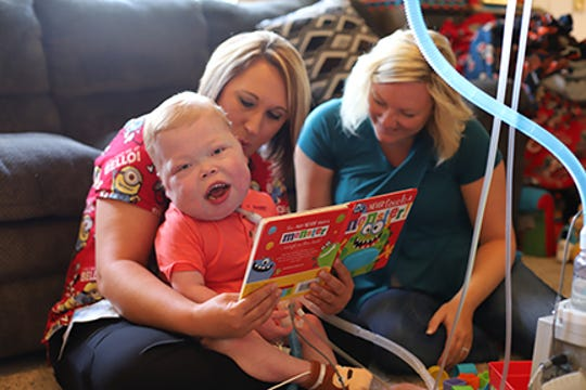 Cayden working with his nurse, Stacy Mahley, LPN, and his occupational therapy assistant, Lindsay Martin, OTA.