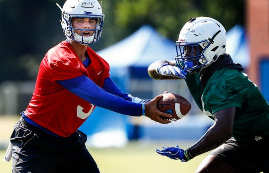 University of Memphis quarterback Brady White (left) hands of to running back Patrick Taylor Jr. (right) during the first day of practice for the 2018-19 season.