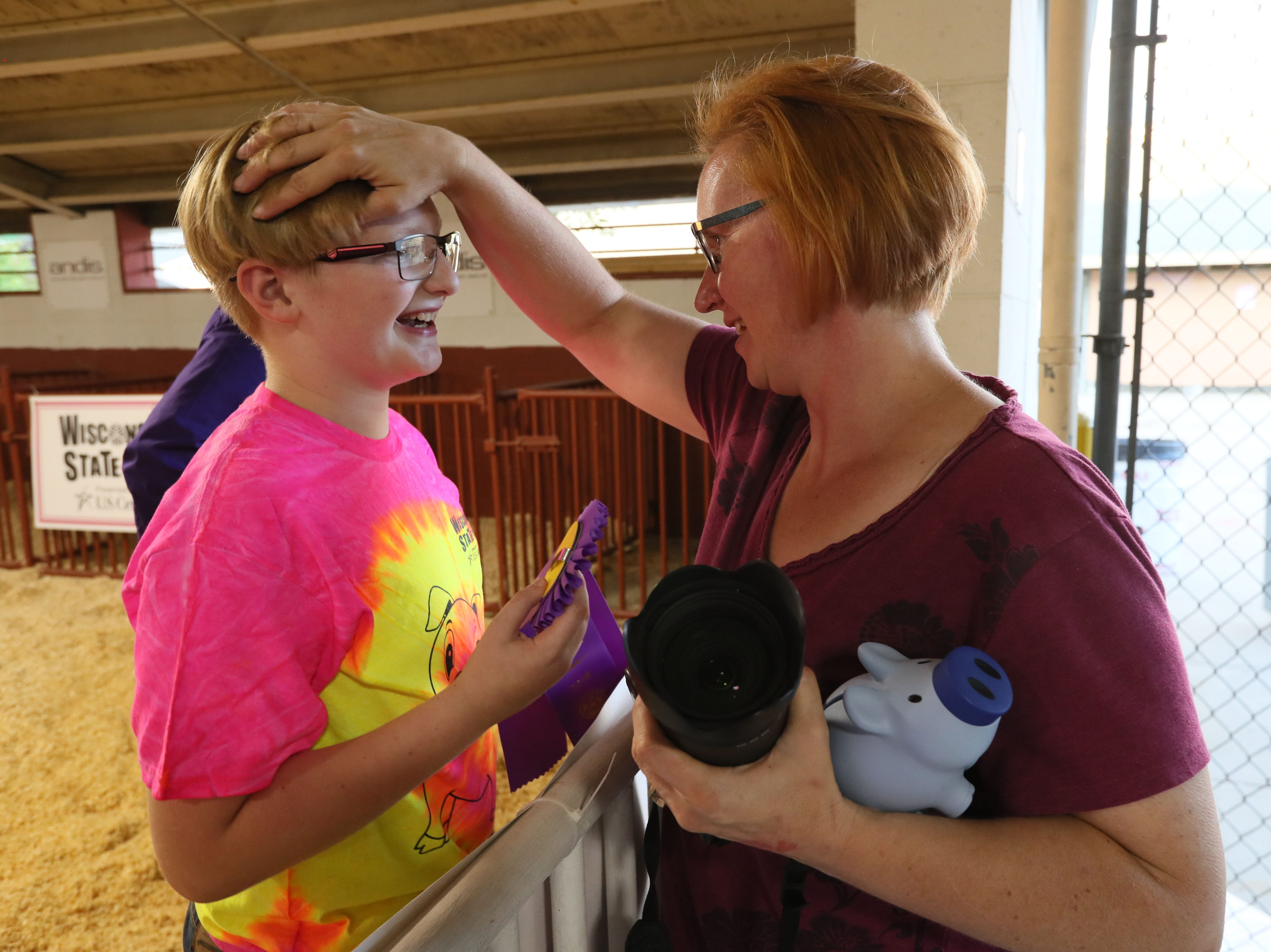 During Wisconsin State Fair's All for One Swine Show, youth with intellectual disabilities got to show a pig with the help of experienced mentors. Sam Incha, 10, of Cambridge, gets congratulations from his mom Cindy after winning an award for showing a pig.