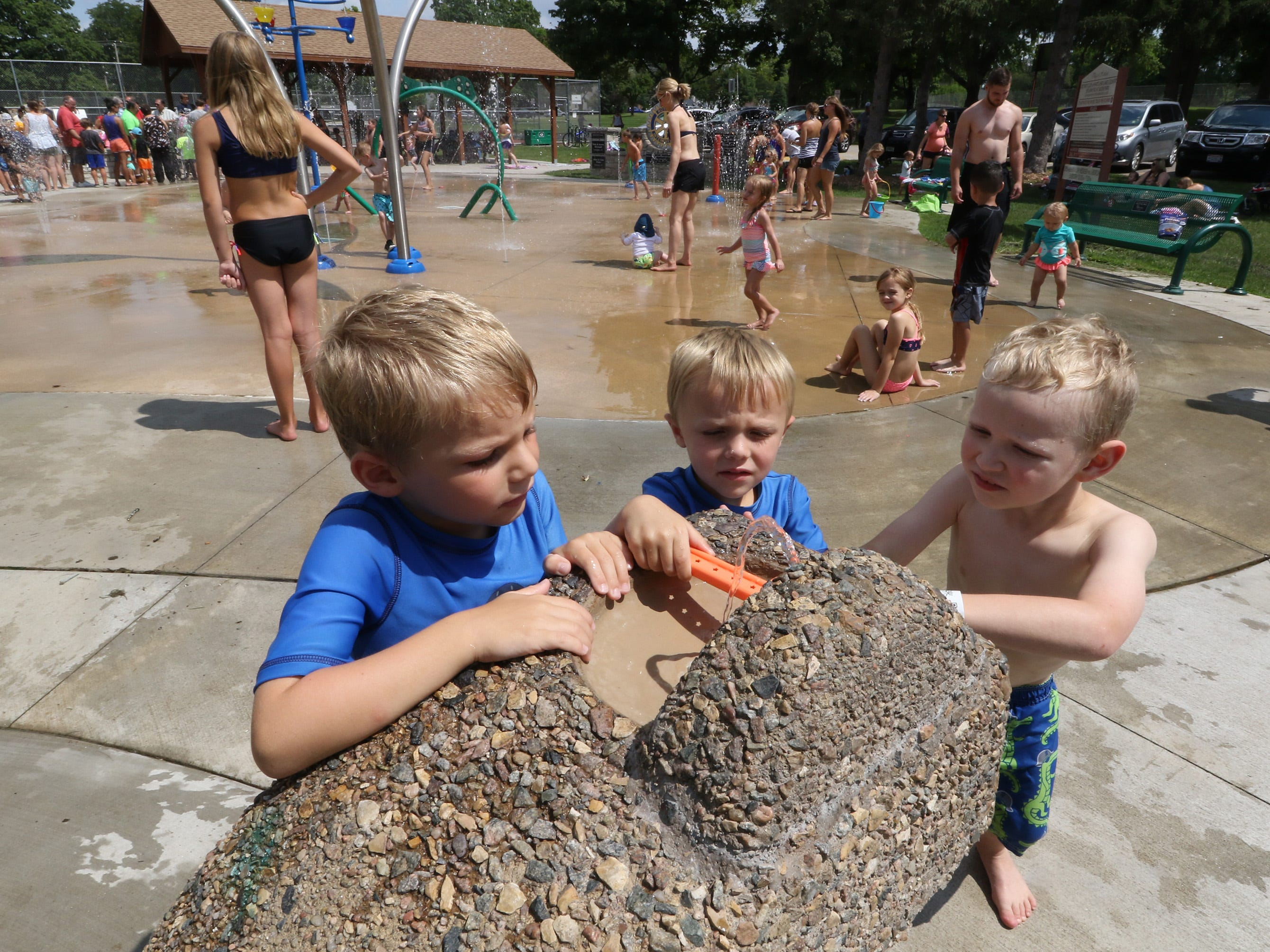 Jack Adams (left), Alex Adams and Fischer Paul play with the water fountain at the Lake Country Rotary Splash Pad in Nixon Park in Hartland on Aug. 3. The Rotary hosted an Appreciation Day with a free hot dog lunch, music and prizes.