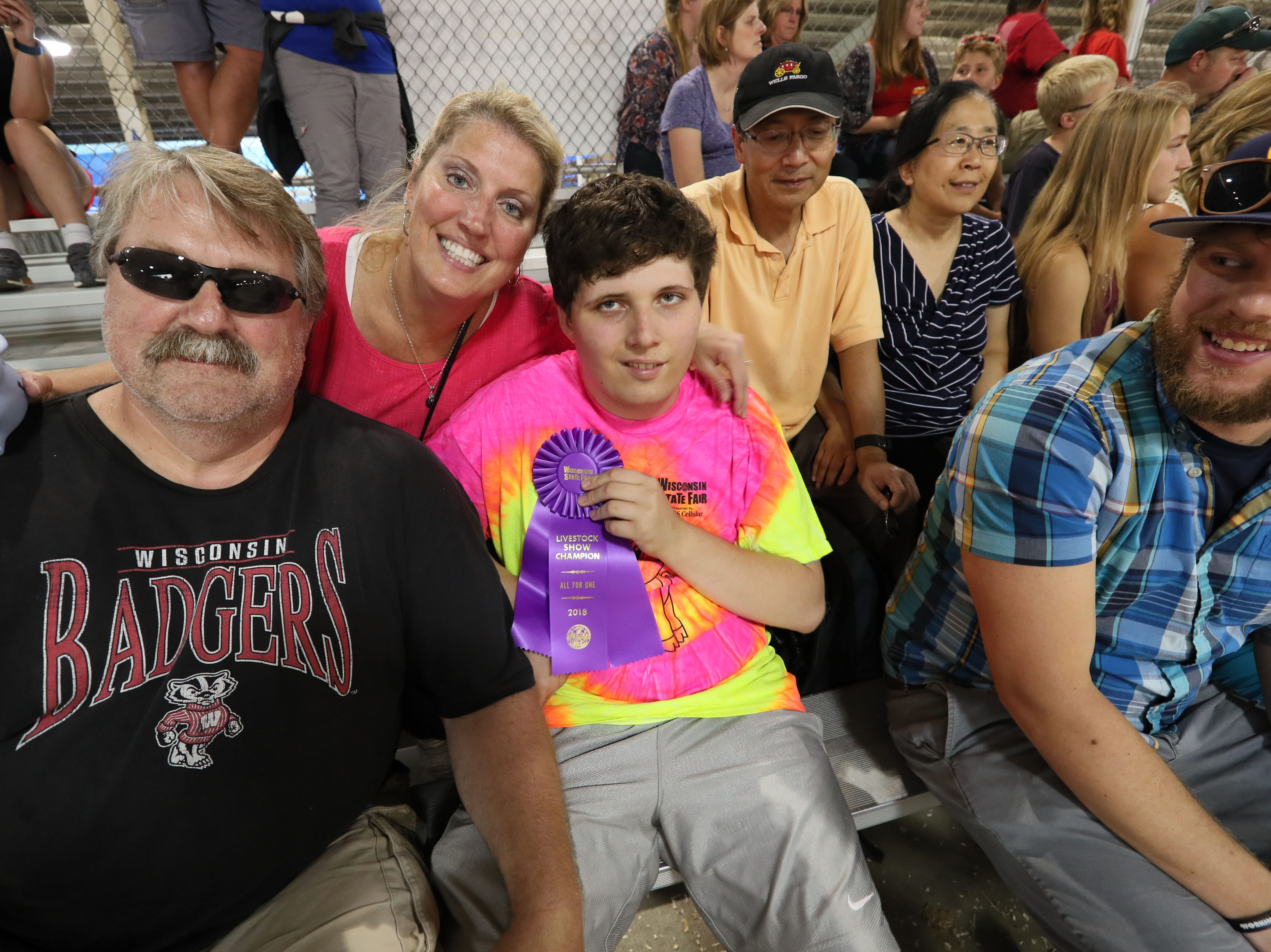 Clint Kuri (left)  and his wife Kathy Kuri (center) of Muskego, pose with their son Alex Kuri (right) age 17, who holds his award he won for his skill in showing a pig at Wisconsin State Fair. During the All for One Swine Show, youth with intellectual disabilities could show a pig with the help of experienced mentors.