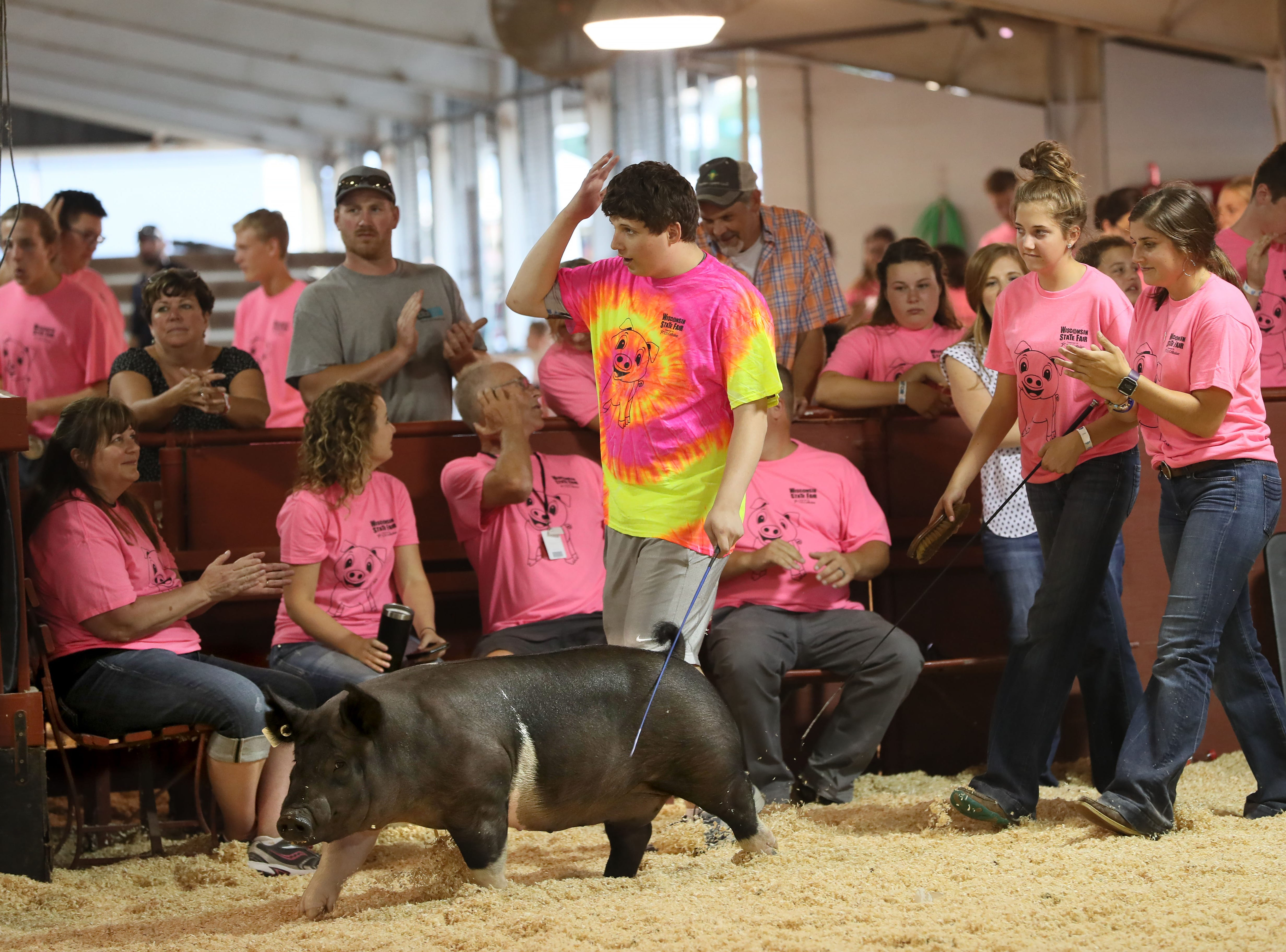 At Wisconsin State Fair, Alex Kuri, 17, of Muskego, shows a pig named Oakley,while being coached by mentors, Elysa Doherty (right), 19, and her sister Isabelle Doherty, 14, both of Johnson Creek.