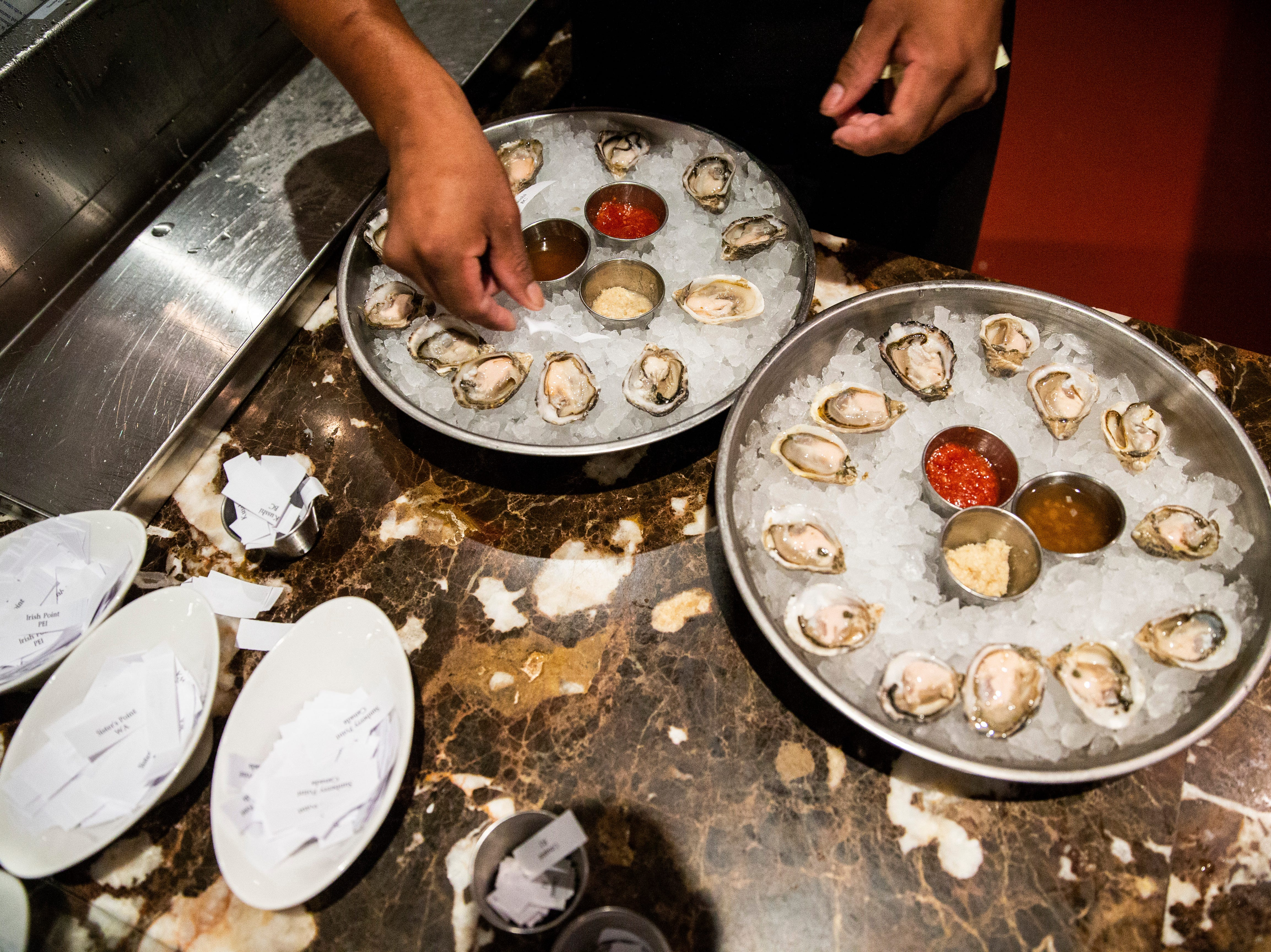 Ruben Ramos places a piece of paper that designates the oyster varieties for dinner guests at Sea Salt in downtown Naples on Thursday, August 2, 2018.