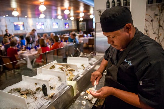 Ruben Ramos shucks oysters for dinner guests at Sea Salt in downtown Naples on Thursday, August 2, 2018.