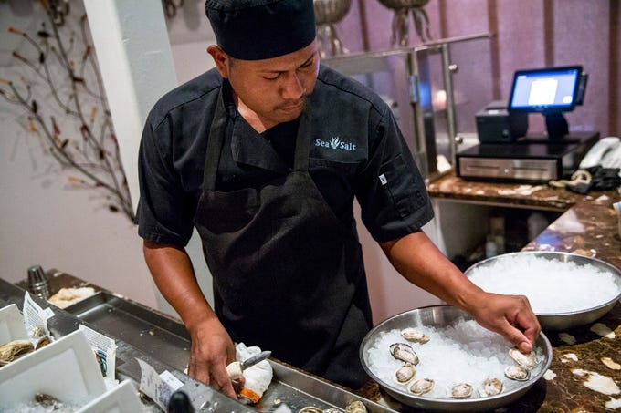 Ruben Ramos plates a freshly shucked oyster while preparing an order at Sea Salt in downtown Naples on Thursday, August 2, 2018.