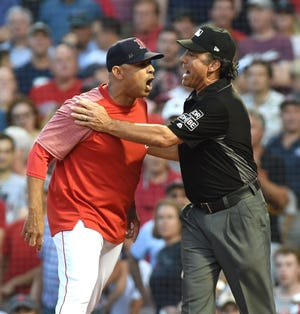 Aug 3, 2018; Boston, MA, USA; Boston Red Sox manager Alex Cora (20) is restrained by umpire Phil Cuzzi (10) after getting tossed out of the game during the first inning against the New York Yankees at Fenway Park.