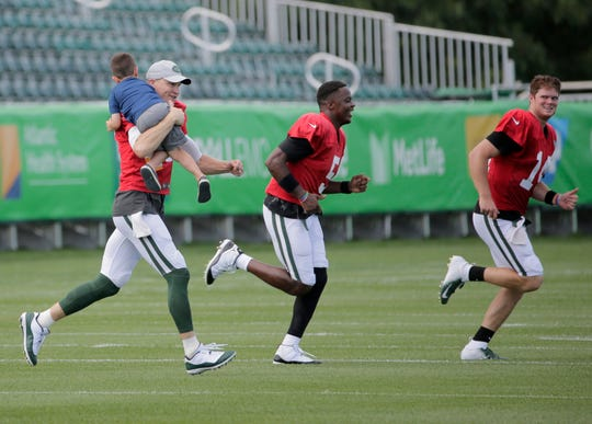 New York Jets quarterbacks Josh McCown, left, Teddy Bridgewater, center, and Sam Darnold run while McCown carries a kid after practice at the NFL football team's training camp in Florham Park, N.J., Wednesday, Aug. 1, 2018. (AP Photo/Seth Wenig)