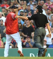 Aug 3, 2018; Boston, MA, USA; Boston Red Sox manager Alex Cora (20) points at umpire Adam Hamari (78) (not pictured) after getting thrown out of the game during the first inning against the New York Yankees at Fenway Park.
