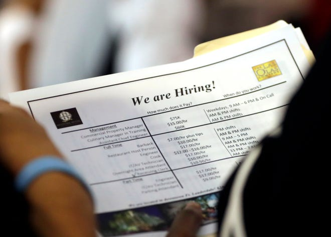 In this June 21, 2018 file photo, a job applicant looks at job listings for the Riverside Hotel at a job fair hosted by Job News South Florida, in Sunrise, Fla.    Economists forecast that employers added 191,000 jobs in July.