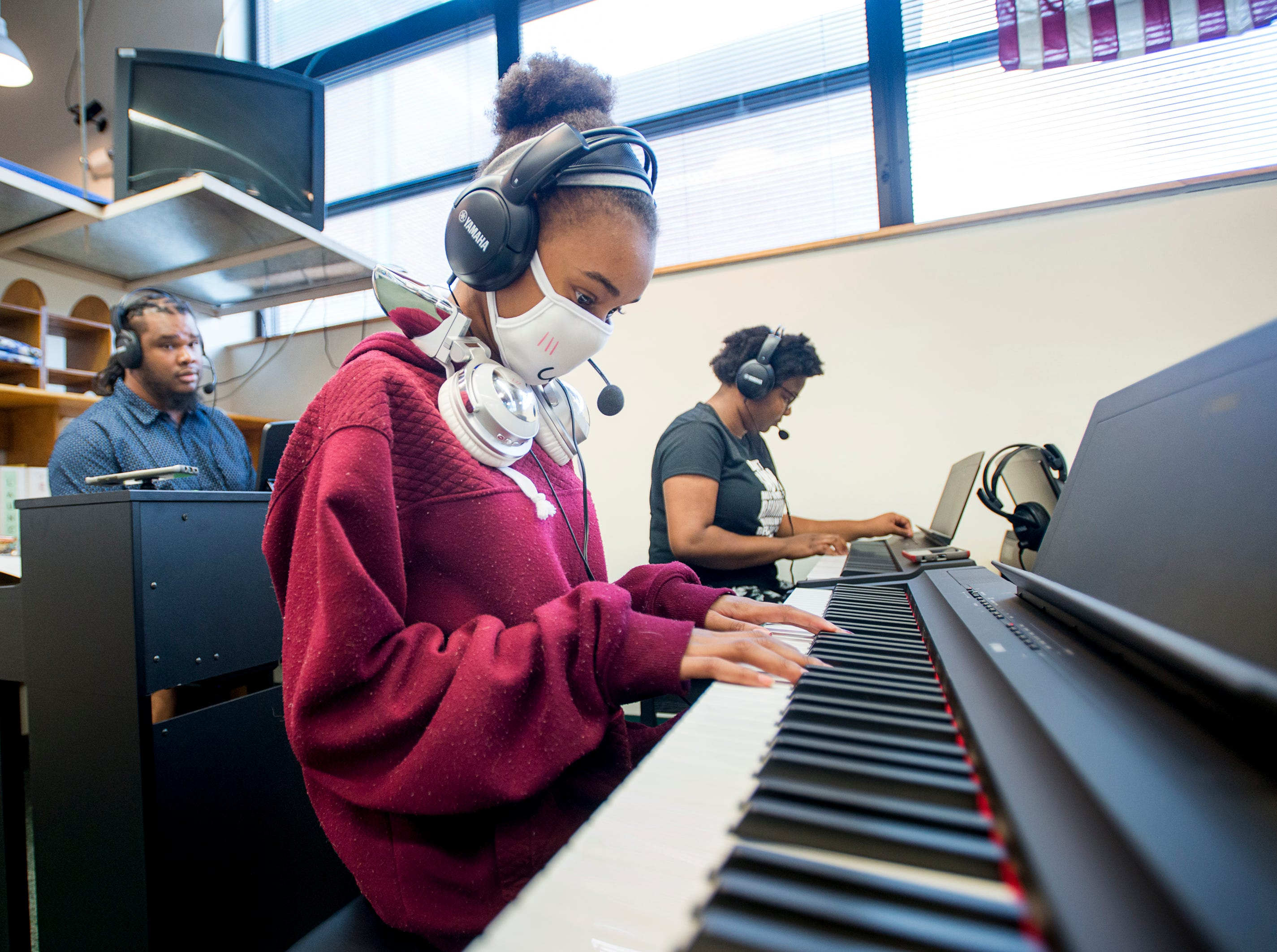 Music teacher Caleb Lovely, left, gives Keira Petterson, 12, center, and Chasity Patterson, 14, a test run of the new piano studio at Warrington Middle School in Pensacola on Friday, August 2, 2018.