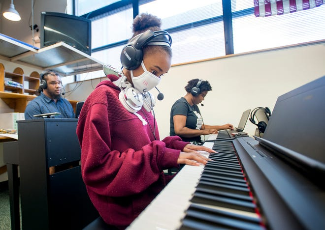 At left, Caleb Lovely, music teacher at Warrington Middle School, gives Keira Petterson, 12, center, and Chasity Patterson, 14, a test run of the new Piano Lab on Friday.
