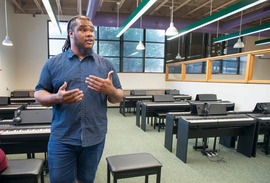 Warrington Middle School music teacher Caleb Lovely sings the praises of the school's new Piano Lab on Friday.