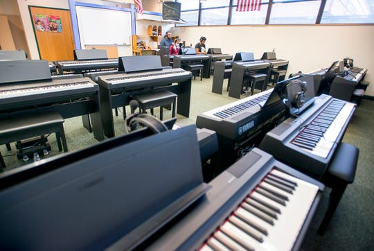 Music teacher Caleb Lovely gives Keira Petterson, 12, center, and Chasity Patterson, 14, a test run of the new piano studio at Warrington Middle School in Pensacola on Friday, August 2, 2018.