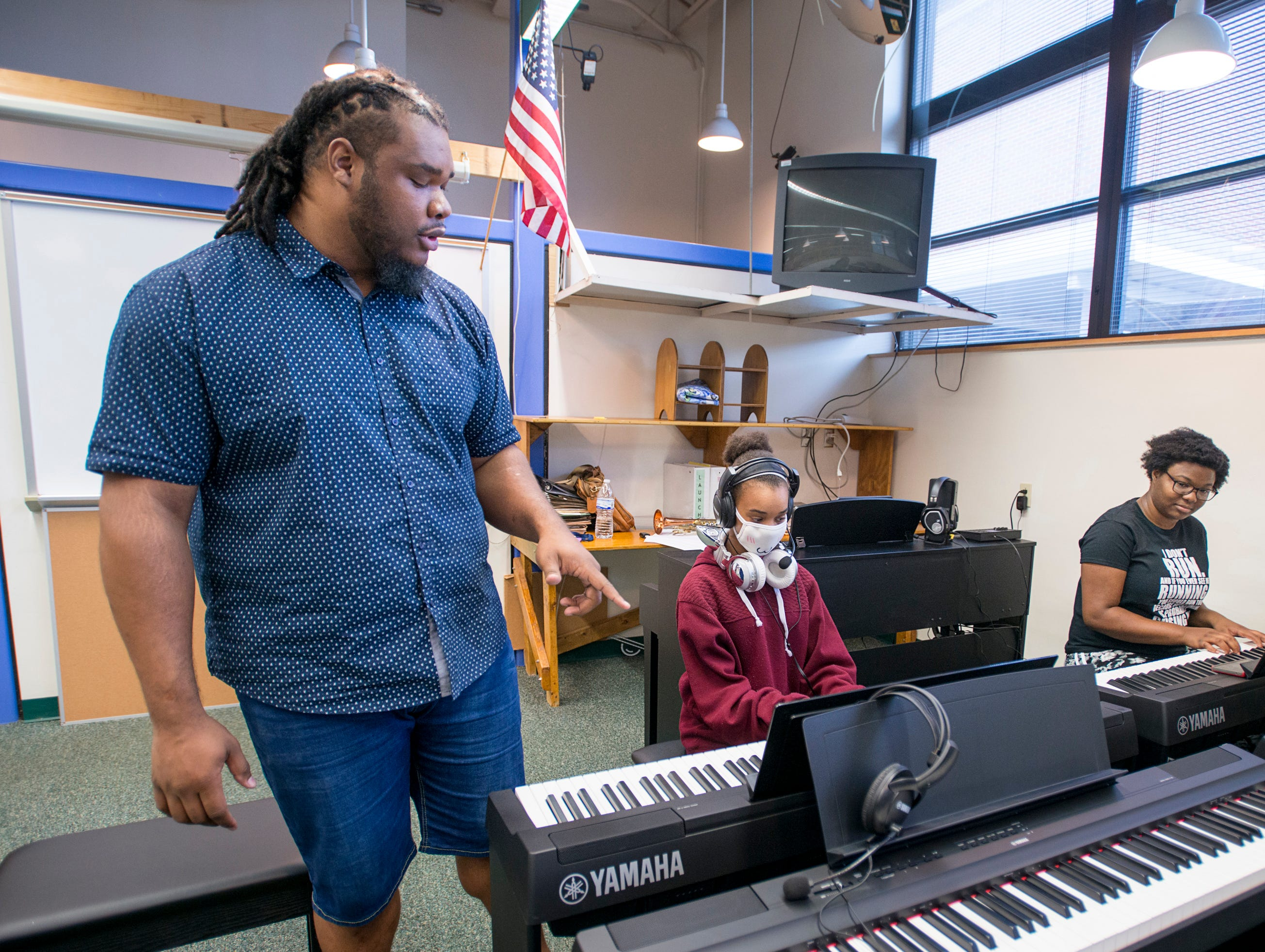 Music teacher Caleb Lovely gives a few pointers to Keira Petterson, 12, center, and Chasity Patterson, 14, as they try out the new piano studio at Warrington Middle School in Pensacola on Friday, August 2, 2018.