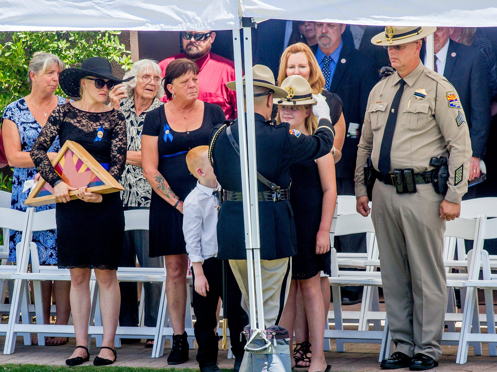 A DPS trooper gives fallen Trooper Tyler Edenhofer's hat to his family and friends on Aug. 3, 2018, during Tyler's funeral at Christ's Church of the Valley in Peoria.