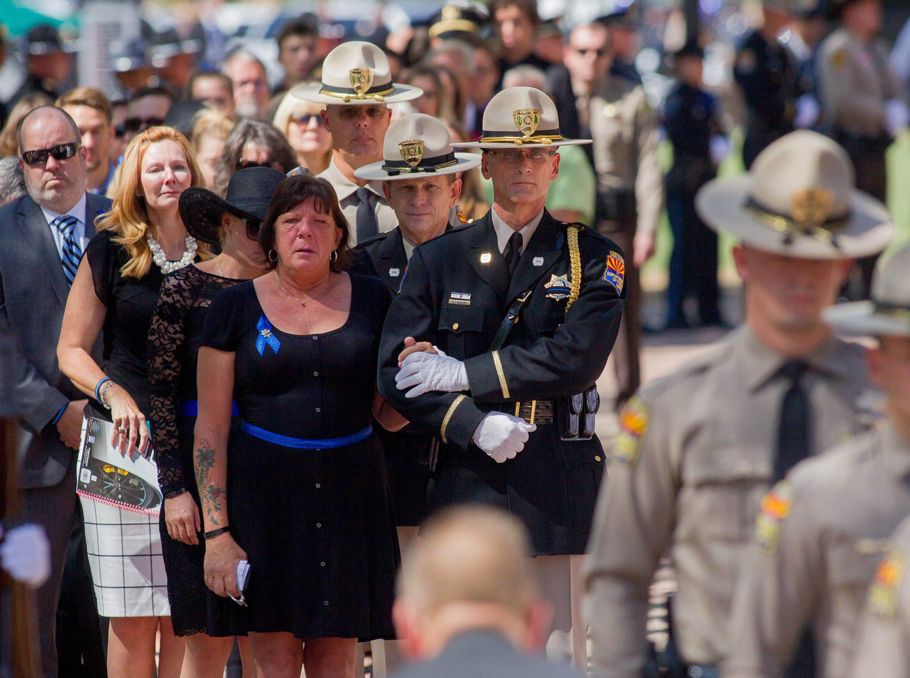 Debbie Edenhofer, mother of fallen DPS Trooper Tyler Edenhofer, is escorted in during the processional for his funeral on Aug. 3, 2018, at Christ's Church of the Valley in Peoria.