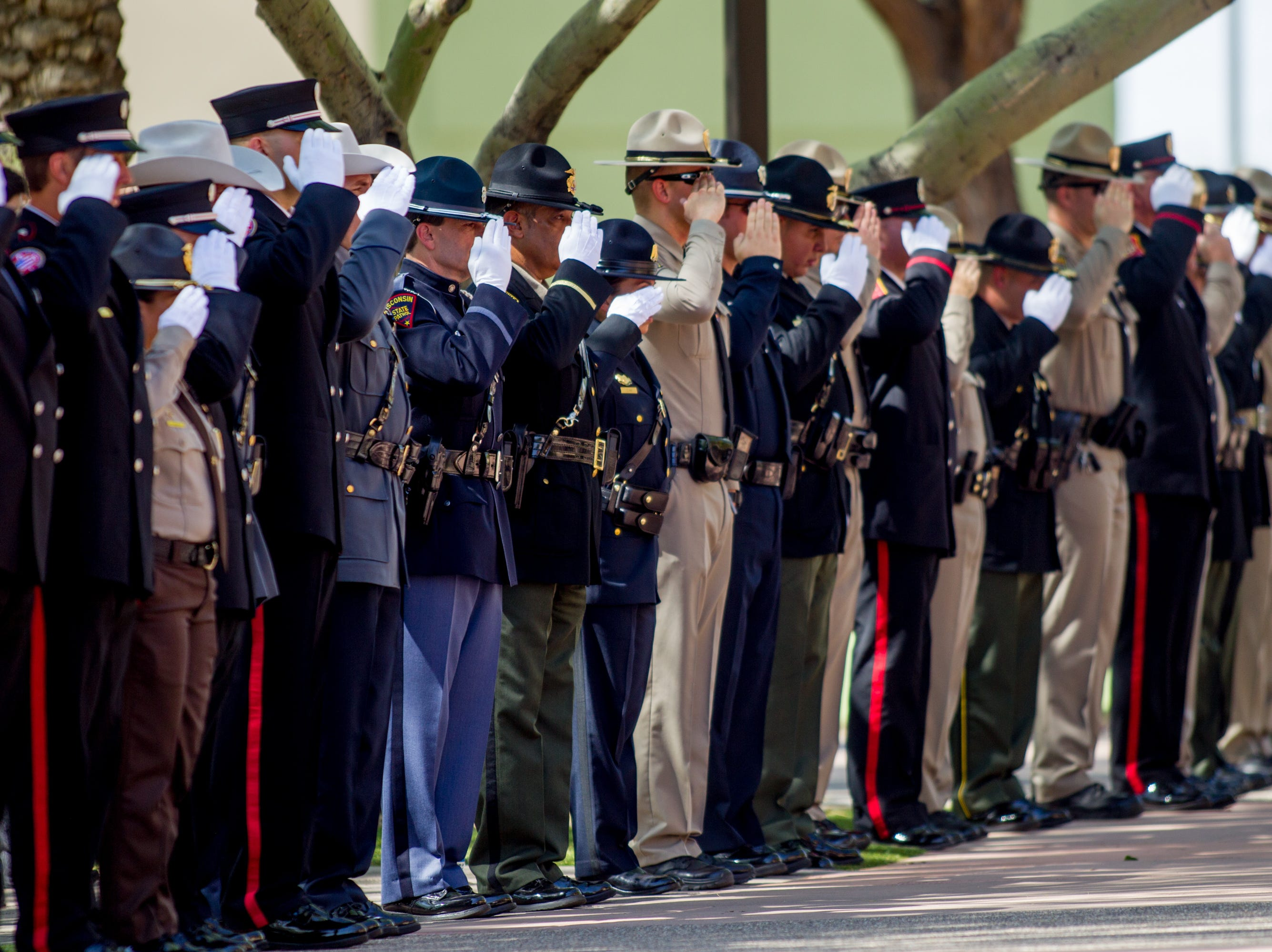 Law-enforcement and emergency personnel salute during the processional for fallen DPS Trooper Tyler Edenhofer's funeral on Aug. 3, 2018, at Christ's Church of the Valley in Peoria.