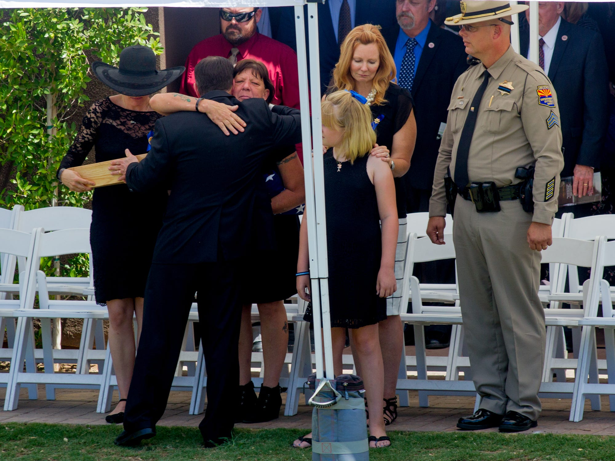 Gov. Doug Doucey hugs Debbie Edenhofer after giving her the flag of Arizona on Aug. 3, 2018 during the funeral for fallen DPS Trooper Tyler Edenhofer at Christ's Church of the Valley in Peoria.