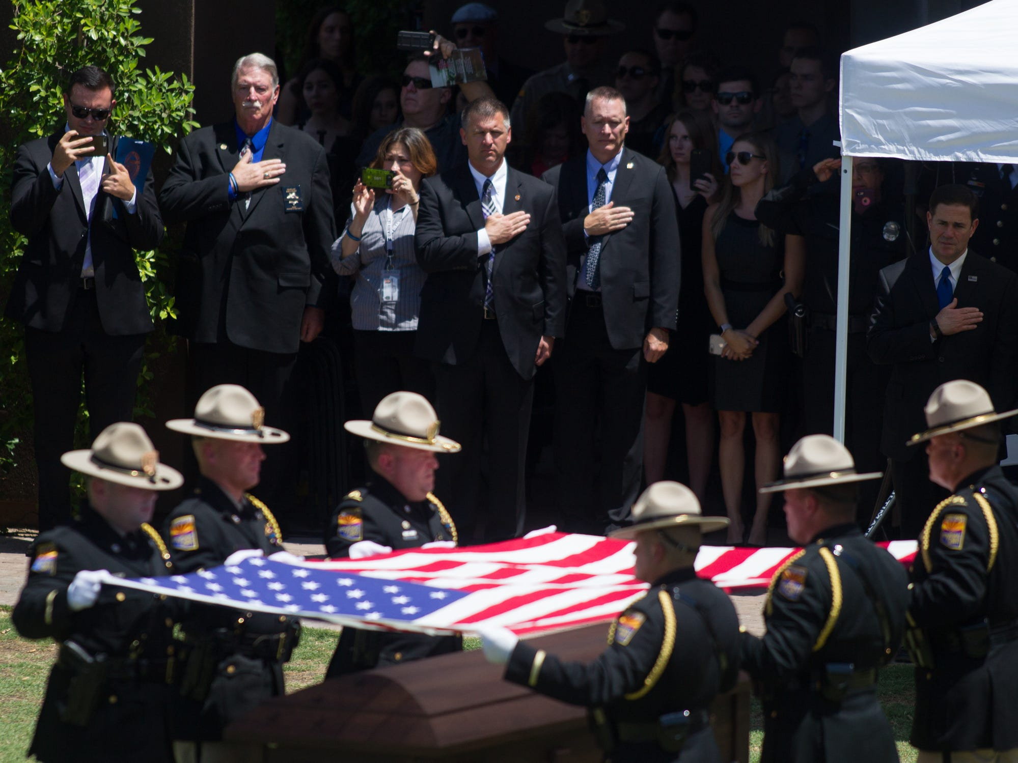 Gov. Doug Ducey (right) watches the folding of the flag on Aug. 3, 2018, during the funeral for fallen DPS Trooper Tyler Edenhofer at Christ's Church of the Valley in Peoria.