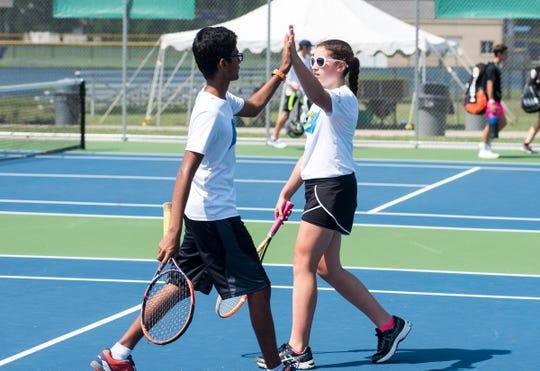 Aditya Damani, left, high-fives his teammate Livvy Heithoff during a Mixed 15U Doubles match Friday, Aug. 3, 2018, at the Francis J. Robinson Memorial International Tennis Tournament at Port Huron Northern High School.
