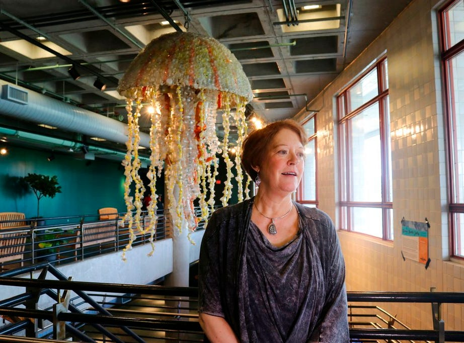 In this photo taken July 26, 2018, Angela Haseltine Pozzi, of Bandon, Ore., describes her project Washed Ashore: Art to Save the Sea at the Audubon Aquarium of the Americas in New Orleans as she stands in front of a giant jellyfish sculpture made from fishing buoys and cut-up water bottles that washed up on the Pacific Coast.