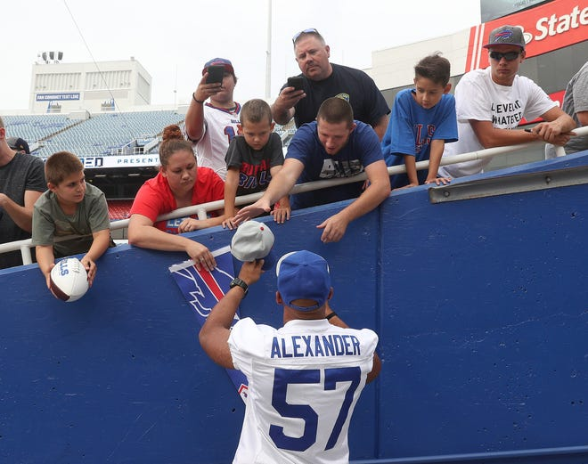 Lorenzo Alexander takes a moment to sign autographs before practice at New Era Field last month. The Buffalo Bills defensive captain said not many players would risk their job protesting during playing of anthem like Colin Kaepernick did.