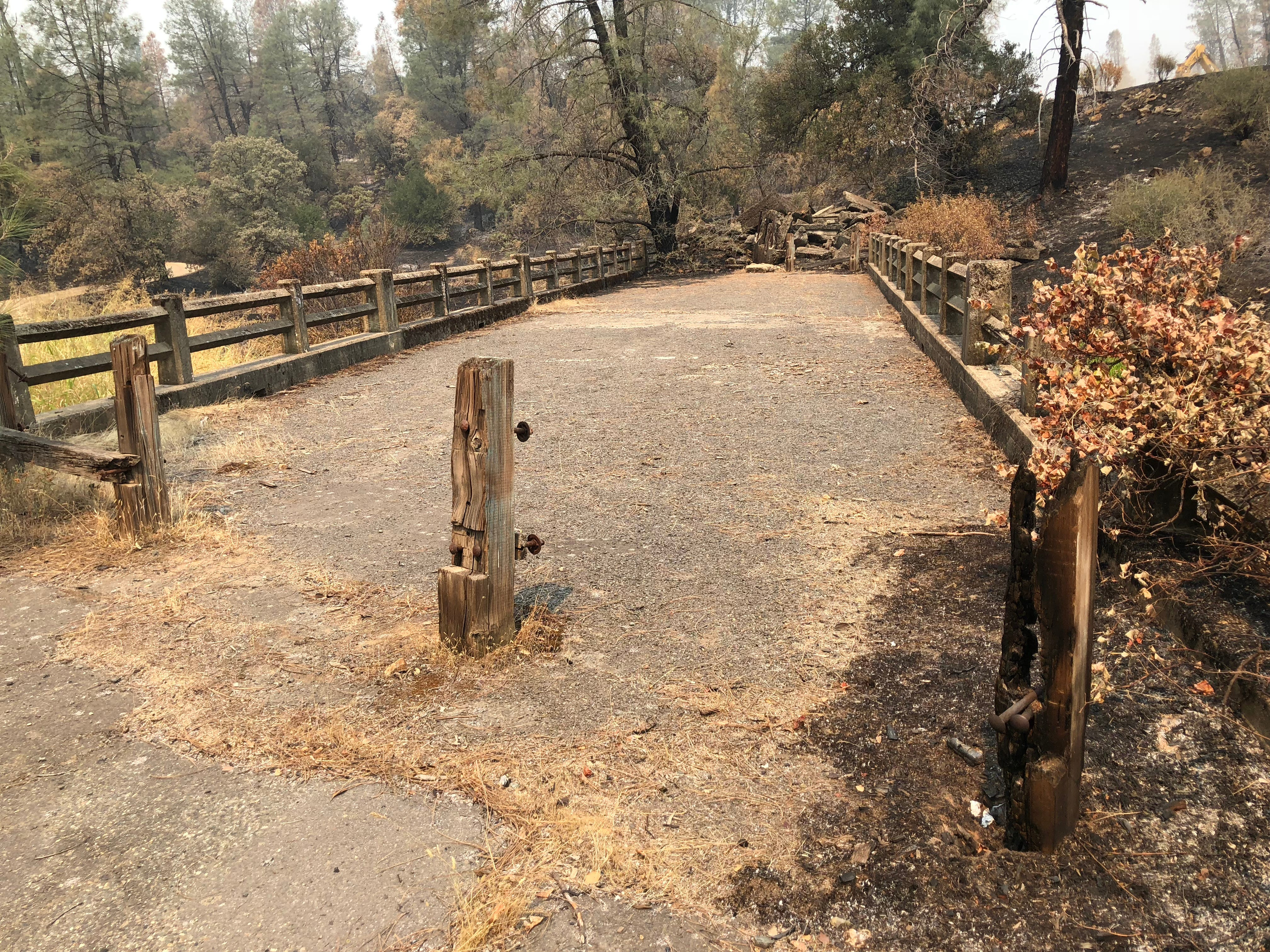 The Middle Creek Connector Trailhead parking area off Highway 299 is closed to the public as officials work alongside the road on Carr Fire recovery efforts. The area is fairly burned with the far end of this bridge having collapsed. Fallen trees partially obscure the path to the parking area.