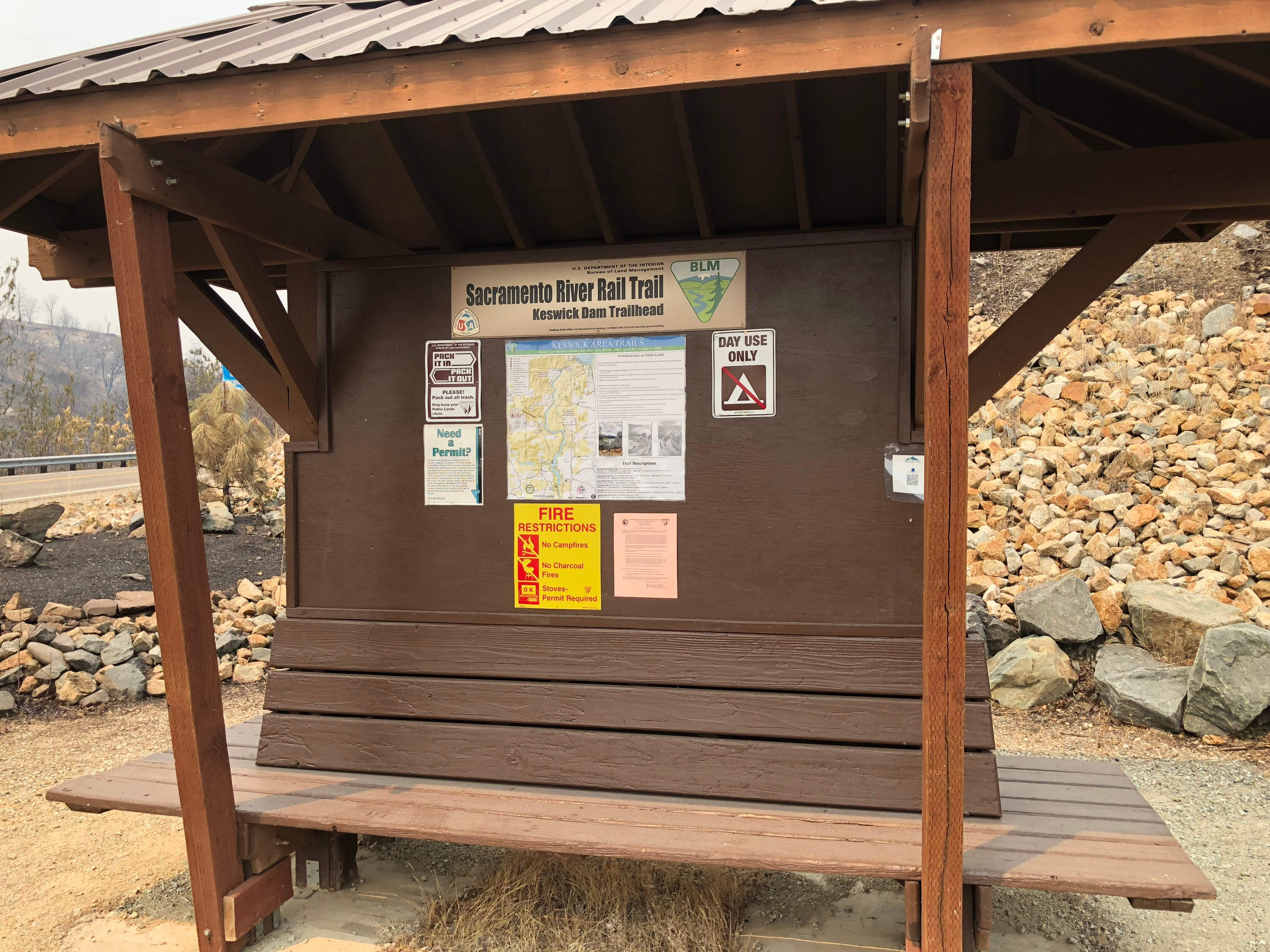 This Keswick Dam Trailhead, west of the dam, has downed power lines and significant fire damage nearby. The trailhead is inaccessible to the public. The bathroom facility near the parking area appears undamaged. This parking lot also serves as the starting point for the Trail 58 French Fry loop.