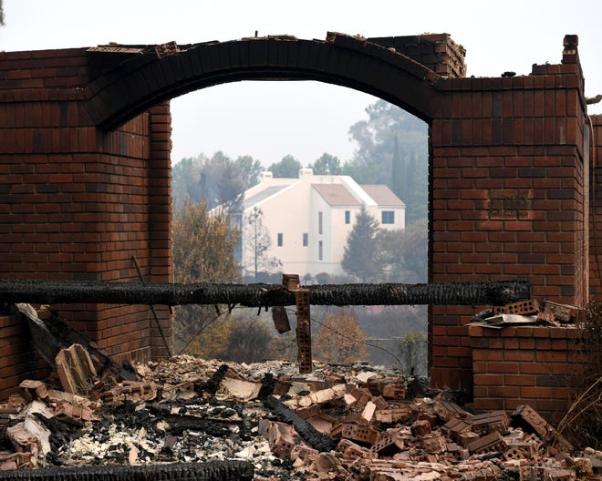 A Redding home that survived the Carr Fire can be seen in the distance between the remaining frame of home that was destroyed.