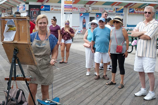 A crowd gathers to watch plein air artist Alison Menke paint on the Boardwalk during 2017's Quick Draw Contest, where artists paint against the clock and compete for cash prizes.