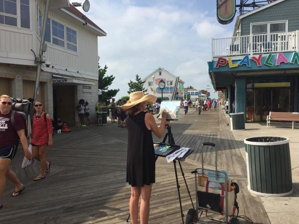 Artist Maggii Sarfarty of Easton captures the bustling Boardwalk in downtown Ocean City Sunday during Artists Paint OC 2017 plein air event.
