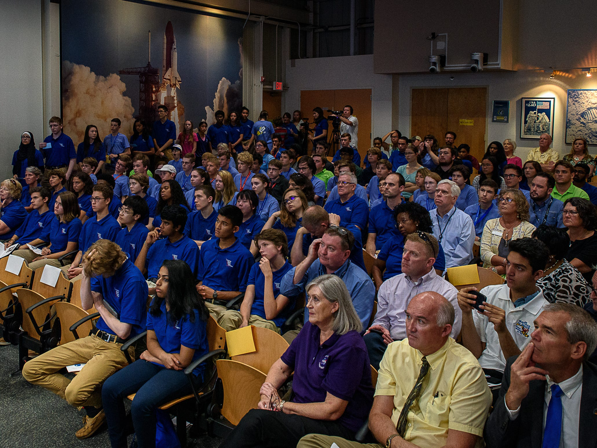 Facilitator Victoria Danna and a student from The Virginia Space Flight academy pose a question to astronaut Andrew Feustel in front of the packed auditorium at Wallops Visitors center. Students at Wallops Flight Facility spoke to crews while aboard the International Space Station as part of NASA's Year of Education on Station program on Aug. 2, 2018.