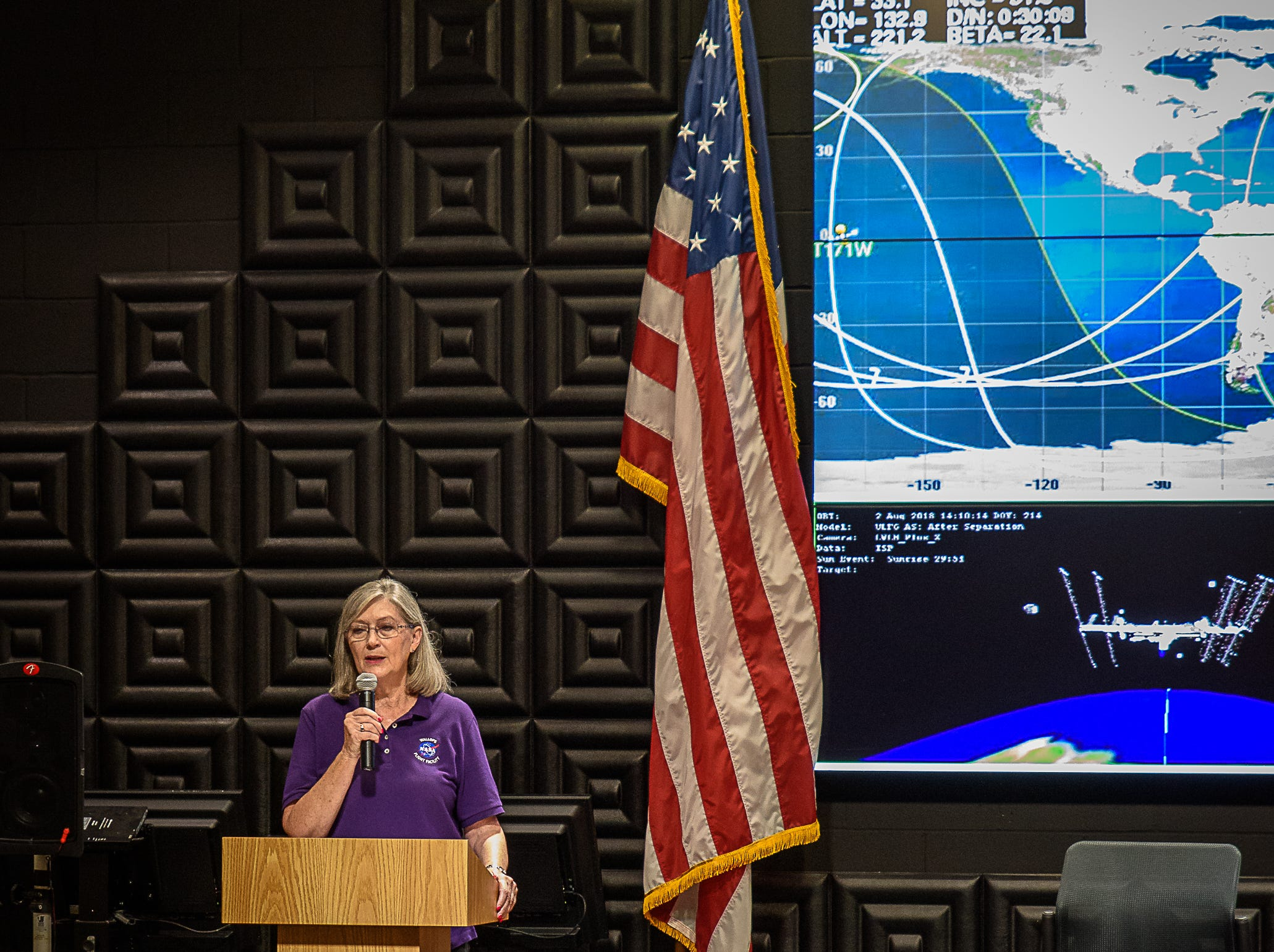 Dr. Joyce Winterton speaks in front of a crowd of people at the NASA Wallops Flight Facility in Virginia. Students spoke with astronauts aboard the International Space Station as part of NASA's Year of Education on Station on Aug. 2, 2018.