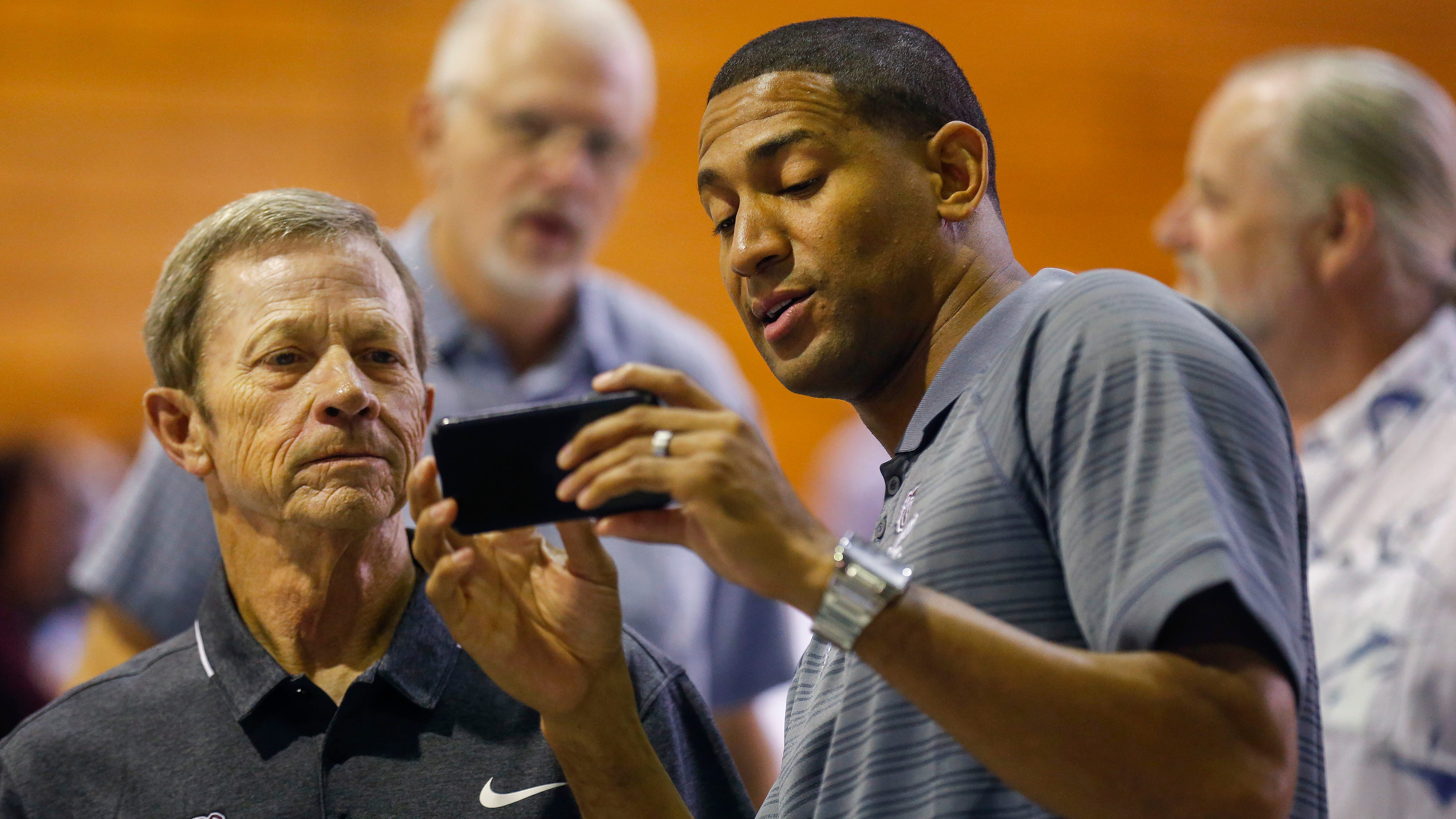 MSU head basketball coach Dana Ford, right, looks at Bill Kirkman's phone during the Sneaker Soiree at Hammons Student Center on Friday, Aug. 3, 2018.
