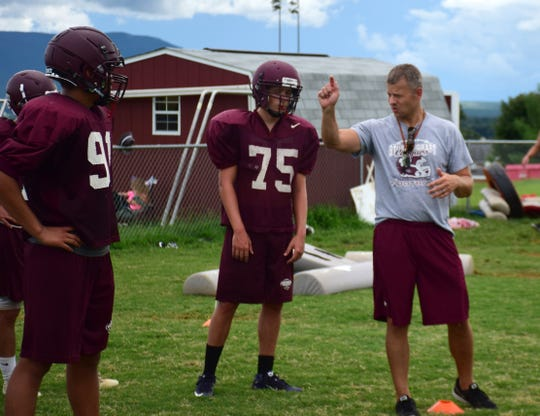 Stuarts Draft head football coach Nathan Floyd, right, guides his players through a drill during practice in Stuarts Draft, Va., on Thursday, Aug. 2, 2018.