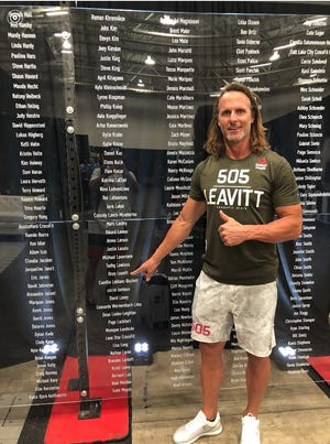 Competitor Ocey Leavitt of Washington City points to his name at the CrossFit Games in Madison, Wisconsin.