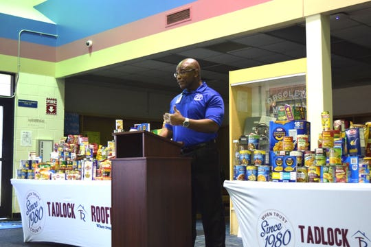 Godby Principal Desmond Cole accepts a $2,000 check and non-perishable food donations from Tadlock Roofing for the school's food pantry.