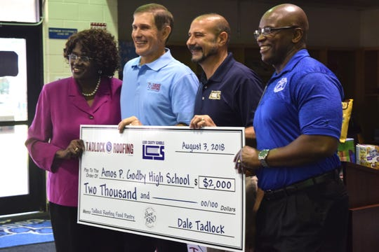 """(From left to right) School Board Member Georgia """"Joy"""" Bowen, Tadlock Roofing President and Owner Dale Tadlock, LCS Superintendent Rocky Hanna and Godby High School Principal Desmond Cole stand with a large check for the school's food pantry."""