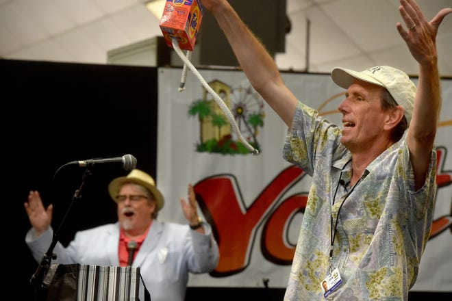 Reporter Tom Kisken performs a magic trick at the Youth Expo after a lesson from traveling stage magician Gus Flamingo at the Ventura County Fair on Thursday.