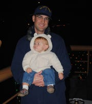 Coast Guard Senior Chief Petty Officer Terrell Horne holds his son during a Christmas cruise onboard the Cutter Halibut in  an undated photo. He was killed in the early morning of Dec. 2, 2012, from injuries sustained during law enforcement operations near Santa Cruz Island.