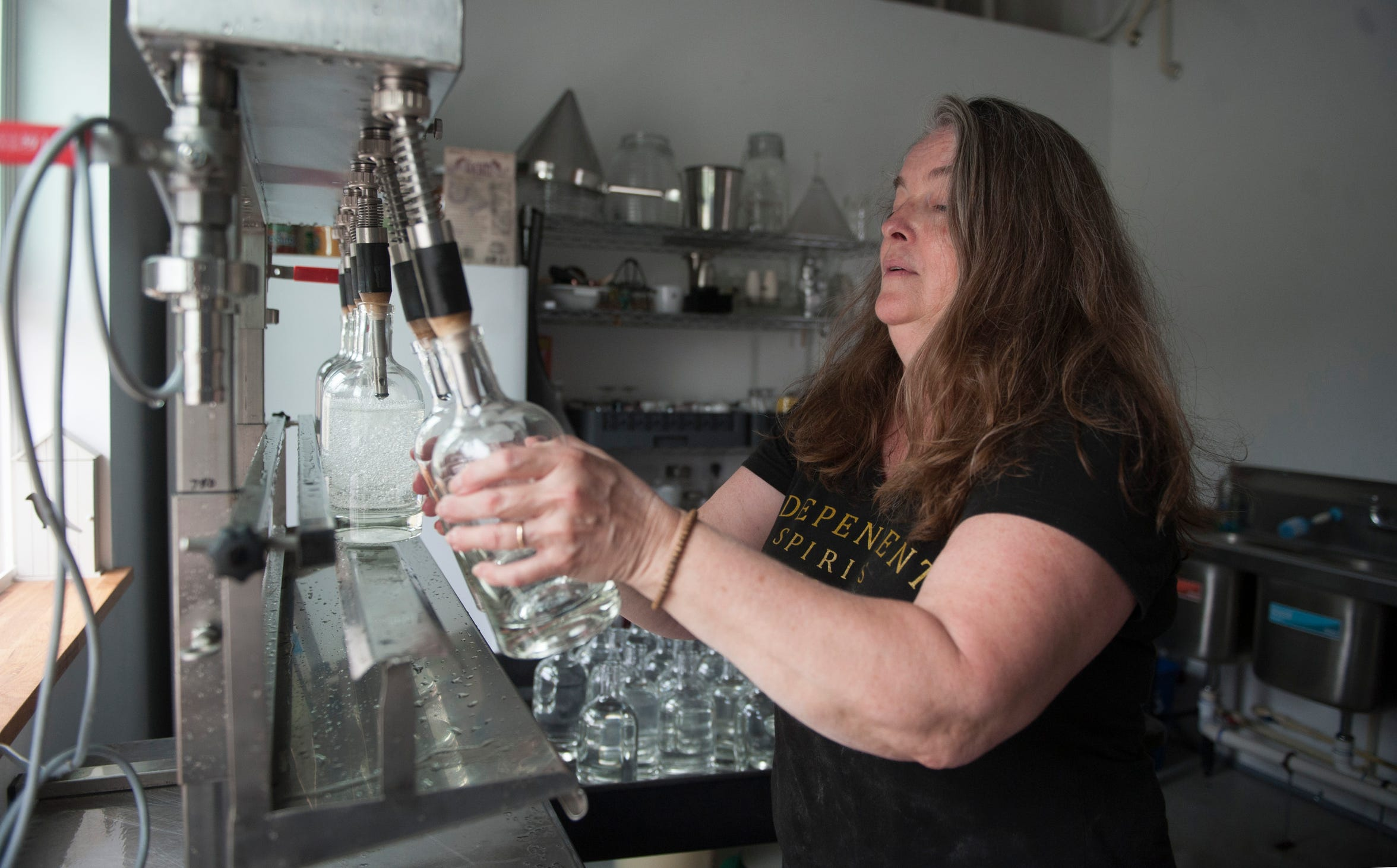 Kerry Thomsen, owner of Independent Spirits Distillery, bottles moonshine in her Woolwich Township distillery.