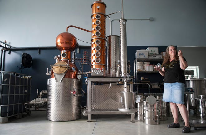 Kerry Thomsen, owner of Independent Spirits Distillery, stands by her still as she produces whiskey in her Woolwich Township distillery.
