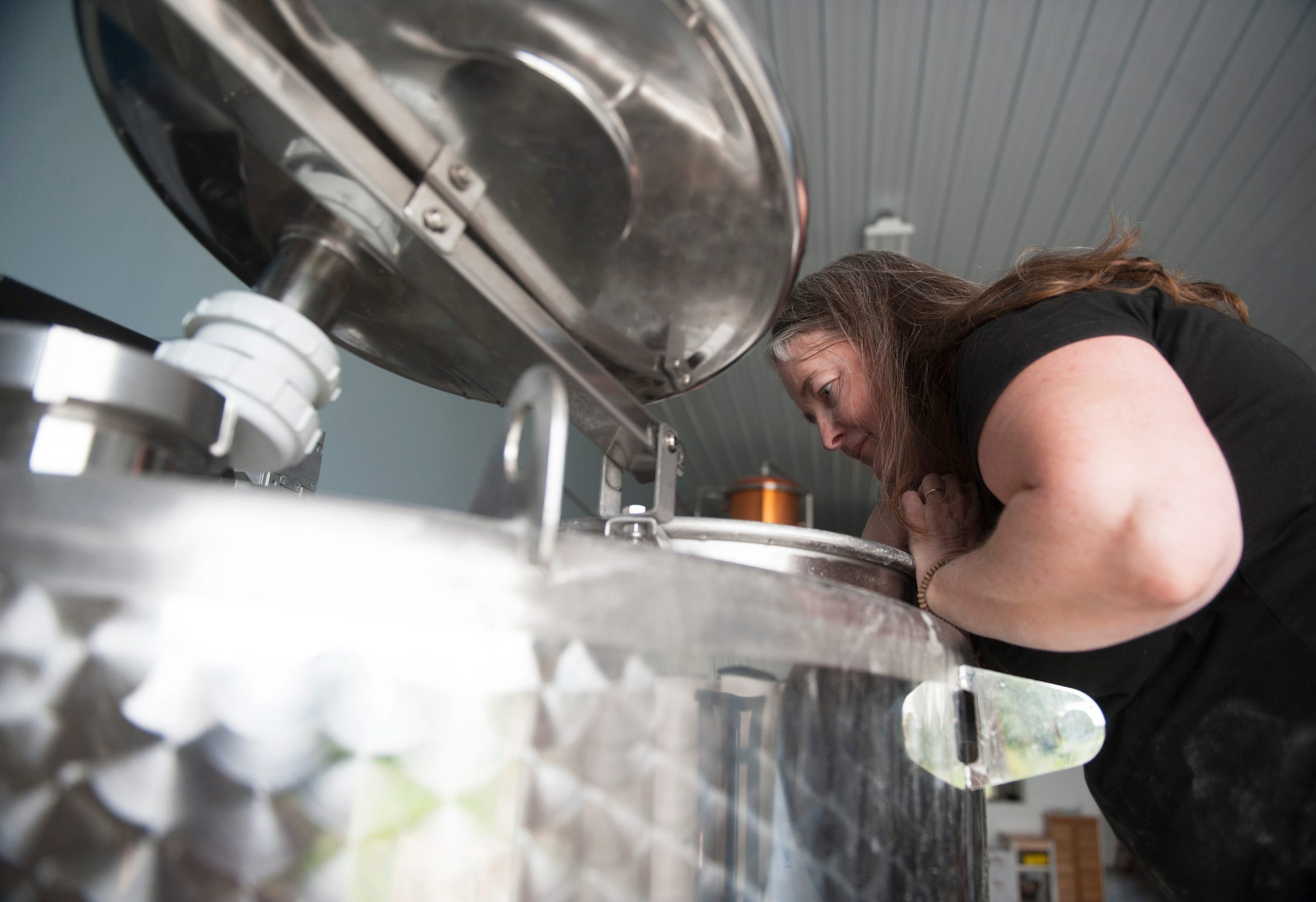 Kerry Thomsen, owner of Independent Spirits Distillery, checks on a batch of whiskey mash in her Woolwich Township distillery.