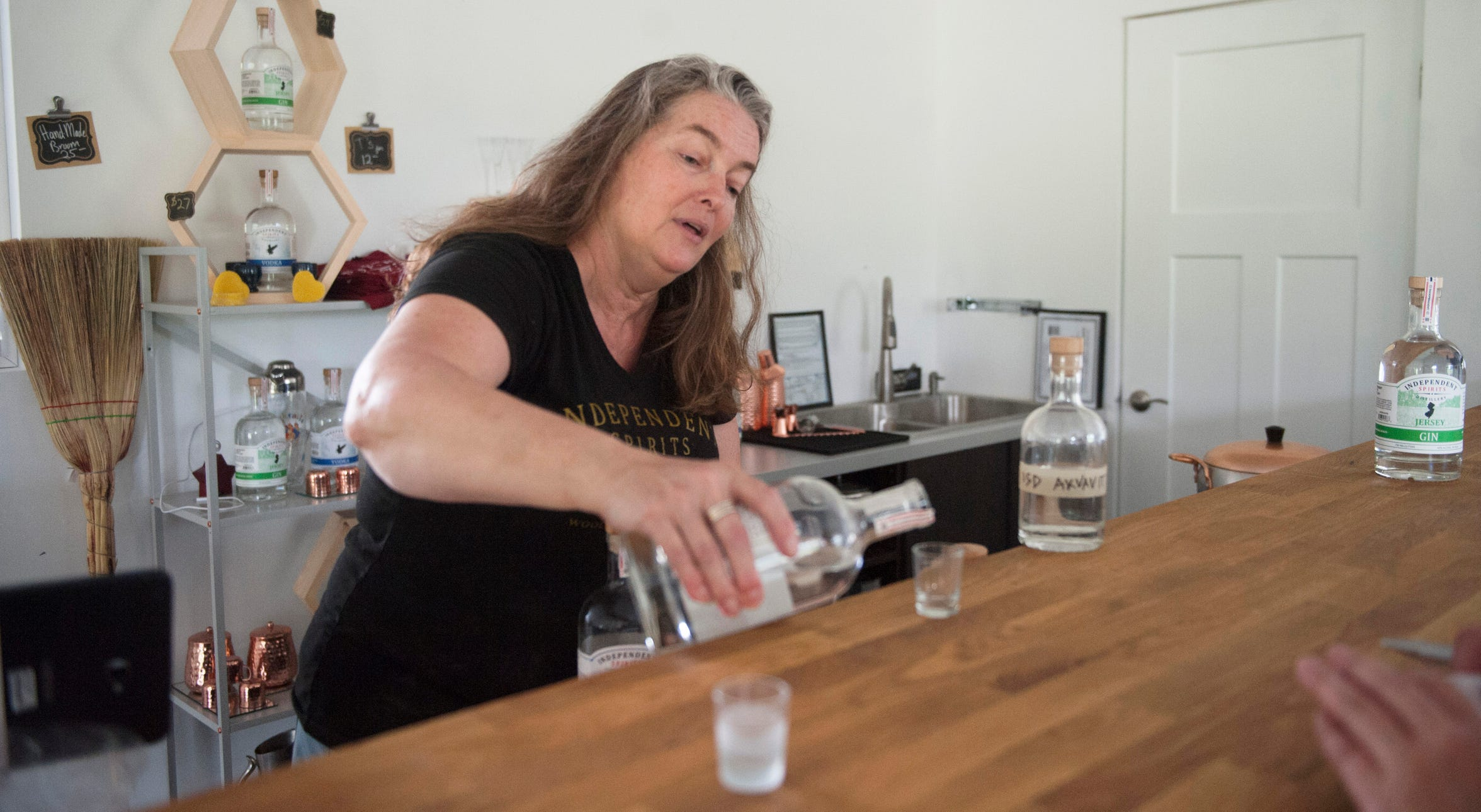 Kerry Thomsen, owner of Independent Spirits Distillery, pours a sample of gin in the tasting room of her Woolwich Township distillery.