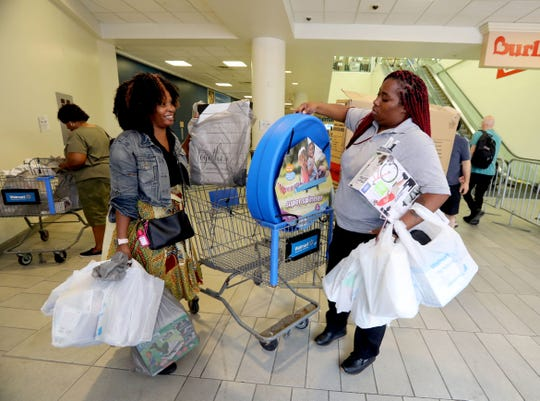 LaShenne Canty of Mount Vernon, left, and Qua Jones of the Bronx unload their shopping cart after shopping at the Walmart in White Plains Aug. 3, 2018. With all remaining items for sale marked down 75%, shopper were able to find bargains as the shelves emptied. Canty, a school teacher, said she spent $450, mostly on school supplies for her classroom. The store closes its doors on Aug. 10th.
