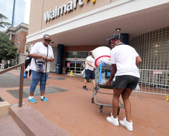 Thaneshia Pearce of White Plains, makes her way to a taxi with a shopping cart full of goods after shopping at the Walmart in White Plains Aug. 3, 2018. Pearce, who was shopping with her mother Sandra, said she spend $197 on a wide variety of products. With all remaining items for sale marked down 75%, shopper were able to find bargains as the shelves emptied. The store closes its doors on Aug. 10th.