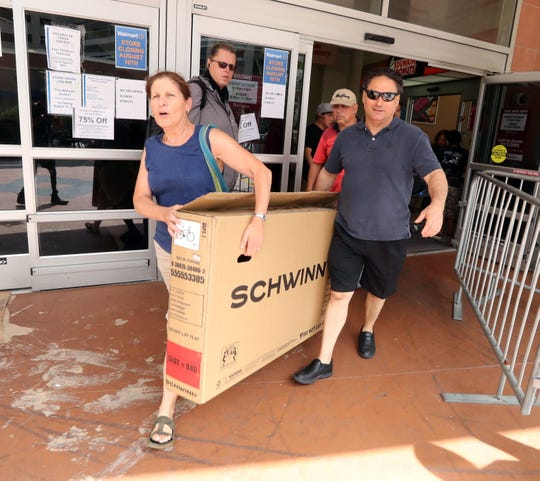 Ava Sherman of Ardsley gets help from fellow shopper Frank Fusco in carrying a bicycle from the Walmart in White Plains Aug. 3, 2018. Sherman said she paid $37 for the bicycle, which she was buying for her husband. With all remaining items for sale marked down 75%, shopper were able to find bargains as the shelves emptied. The store closes its doors on Aug. 10th.
