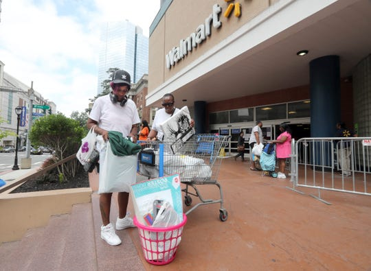 Thaneshia Pearce of White Plains, empties out her shopping cart full of goods after shopping at the Walmart in White Plains Aug. 3, 2018. Pearce, who was shopping with her mother Sandra, said she spend $197 on a wide variety of products. With all remaining items for sale marked down 75%, shopper were able to find bargains as the shelves emptied. The store closes its doors on Aug. 10th.
